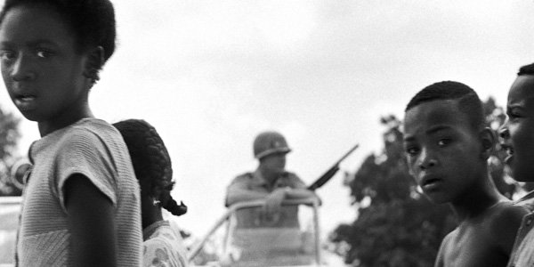 Marching children framing a state police sharpshooter. Maria Varela Near Jackson, Mississippi, 1966