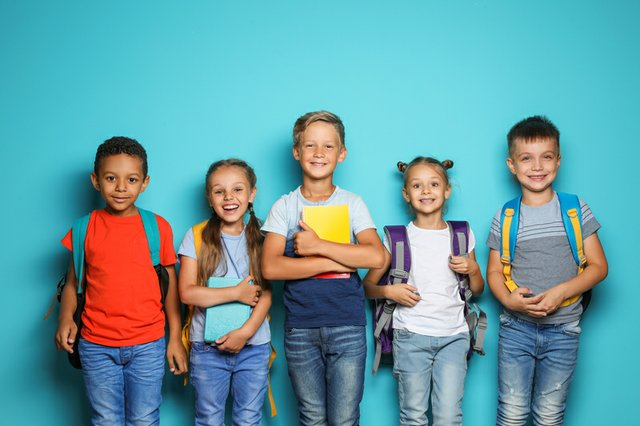 Group of little children with backpacks and school supplies on color background