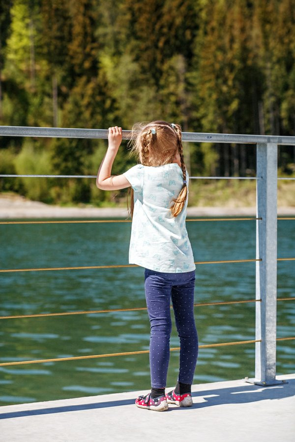 A little girl stands and looks at the lake and the forest. Conce